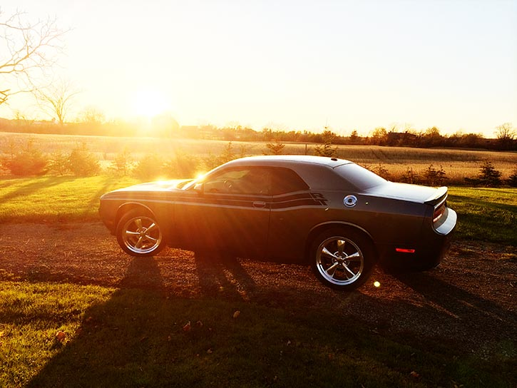 A dodge Challenger sitting on a country road with a setting sun behind it