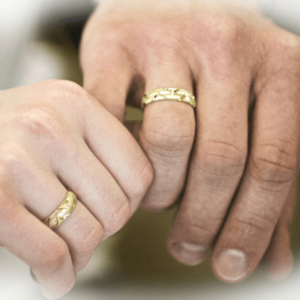 Couple holding hands wearing wedding rings