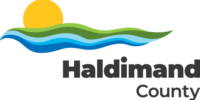 Haldimand County logo. A yellow sun rising or setting atop green and blue waves. Haldimand County in black lettering below.